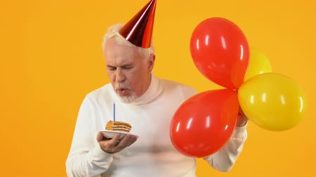díszítés : Smiling pensioner blowing cake candle falling confetti, birthday celebration Stock mozgókép