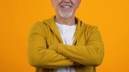 érettség : Smiling mature man in casual clothes folding arms on orange background, wellness