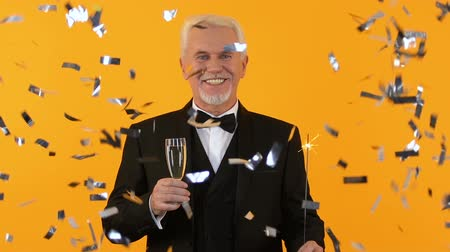 празднование : Successful elderly gentleman holding wine glass and sparkler, party confetti