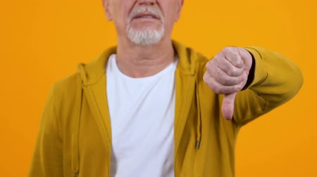 неправильно : Displeased elderly man showing thumbs down, dislike gesture, disagreement sign Стоковые видеозаписи