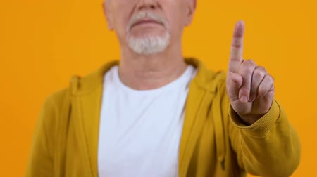rejeitar : Elderly man showing warning gesture finger, rejection sign, pensioner advice