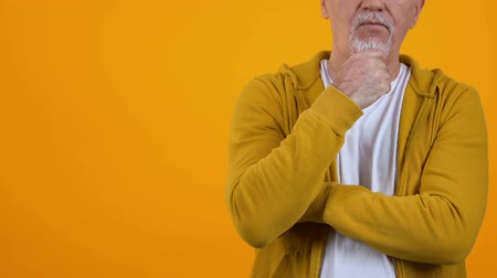 решить : Pensive elderly male touching chin standing against bright background, decision Стоковые видеозаписи