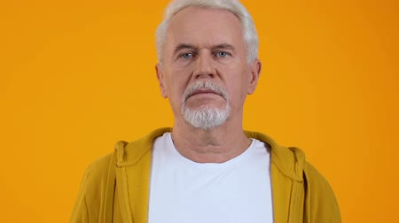 confusão : Surprised retired man on orange background, shocking news, unexpected problem Stock Footage