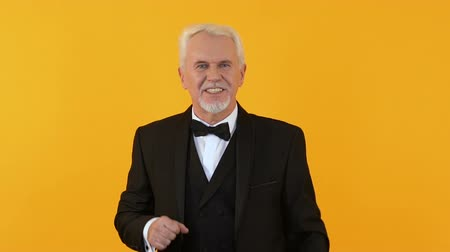 празднование : Playful male pensioner in elegant suit dancing on orange background, party fun