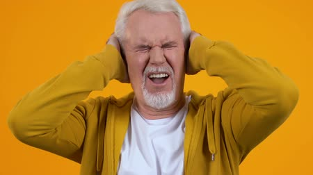 dojemný : Aged pensioner covering ears suffering loud noise, conversation nervousness