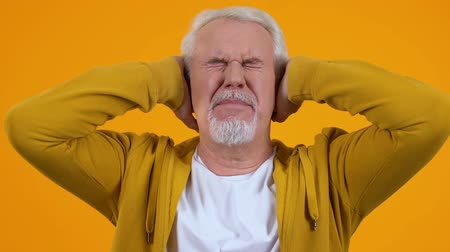 dialog : Senior man covering ears by hands tired of loud conversation noise, pressure