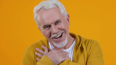 olgun : Kind male pensioner admiring on orange background, looking with love, good news