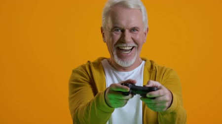 konzol : Happy senior male playing video game console, retirement hobby, entertainment