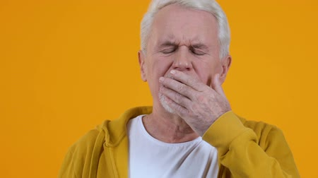 tiredness : Tired pensioner yawning and showing sleep gesture, insomnia exhaustion, rest Stock Footage