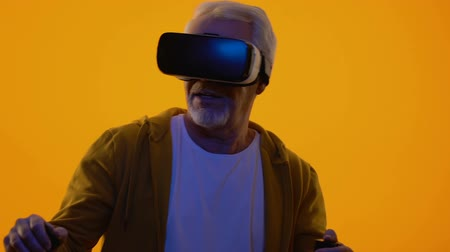 очки : Aged man wearing virtual reality headset, cyberspace game, entertainment device Стоковые видеозаписи