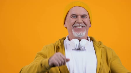 mókás : Positive old man in stylish cloth and headphones dancing, feeling young, leisure