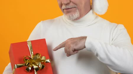 celebration : Mature man pointing at red present box, christmas celebration, holiday surprise