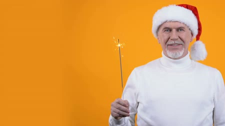 рекламный : Male pensioner santa hat and bengal light orange background, christmas greeting