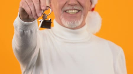 mülkiyet : Man in santa claus hat showing house key closeup, real estate purchase, gift Stok Video