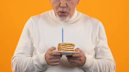 expectativa : Sad retired man blowing cake candle feeling lonely on birthday, disappointment Vídeos