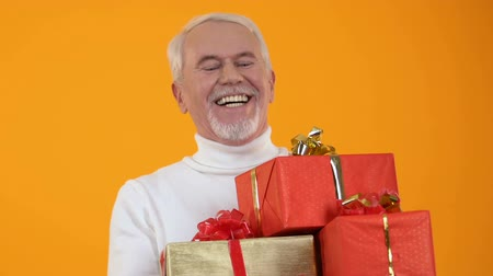 szenteste : Glad senior male holding present boxes in hands, holiday preparation, surprise