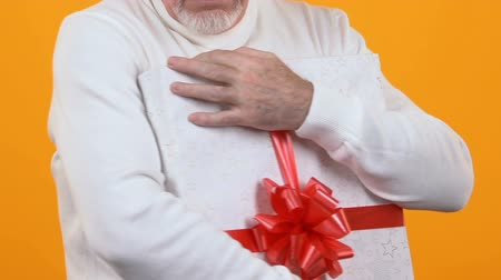 ganancioso : Greedy old man holding wrapped present box, capricious pensioner, souvenir