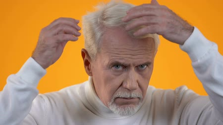 hair growth : Upset old man looking grey hair, baldness treatment, health care, cosmetology Stock Footage