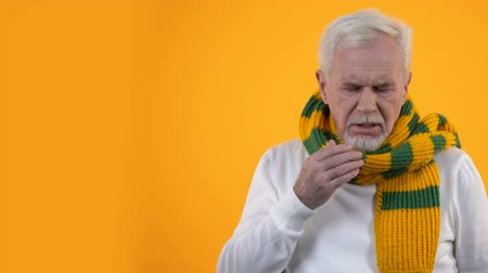 influenza background : Sick aged man in scarf suffering cough, infection disease, sore throat treatment Stock Footage