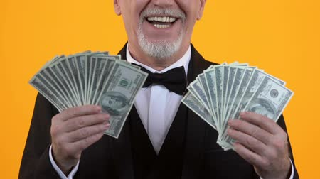 investidor : Rich aged gentleman in suit showing dollars, lottery winner, business income