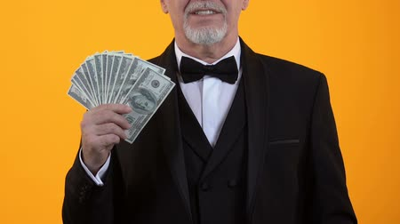 kciuk : Happy elegant male showing thumbs up holding dollars in hand, casino winner Wideo