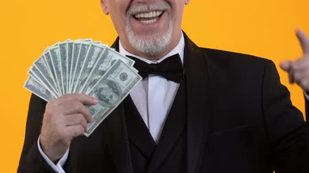 kasyno : Cheerful gentleman pointing at dollars in hand, salary payment, easy credit