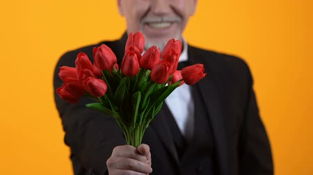 olgun : Smiling senior male presenting red tulips, well-mannered gentleman on date