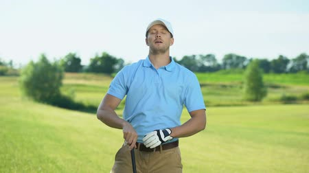 cursos : Cheerful golfer holding club and warming up shoulder mussels before competition Stock Footage