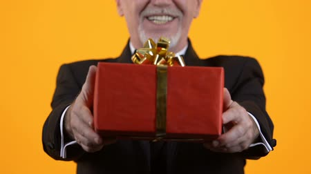 kerstpakket : Senior man showing red gift box, birthday present, holiday surprise, affection