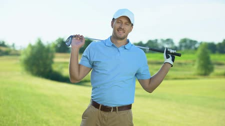 времяпровождение : Confident golf player with club behind back smiling on camera at course, sport