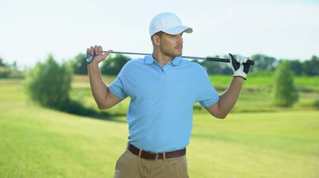 seçkinler : Joyful male player holding golf club behind shoulders, ready to start sport game Stok Video