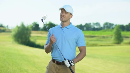 cursos : Happy golf player with club smiling on camera, luxury hobby and sport, activity