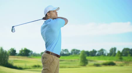 regozijo : Beginner golf player taking swing hitting ball, rejoicing successful shot, luck Stock Footage