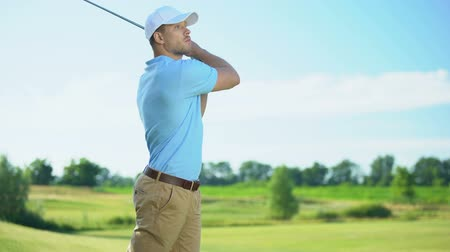 cursos : Young male golf player hitting ball, surprised with unsuccessful shot, bad luck