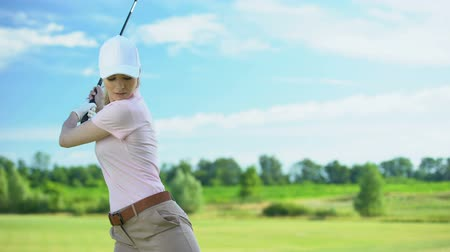 golfjátékos : Female golf player hitting ball with club at course, training and sport, hobby