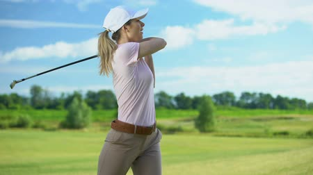 cursos : Young female golfer hitting ball, rejoicing successful shot, gesturing yes sign