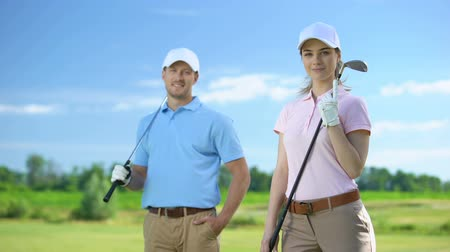 тренер : Beautiful female with golf club and sport coach smiling on camera, free lessons Стоковые видеозаписи