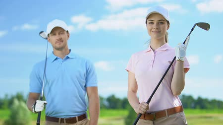 golfové hřiště : Young female golfer with partner holding clubs and smiling on camera, recreation Dostupné videozáznamy