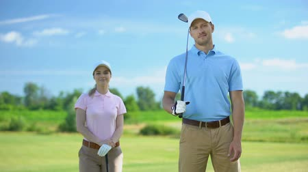 времяпровождение : Handsome golf trainer and female beginner with clubs smiling on camera, sport Стоковые видеозаписи