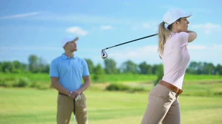 cursos : Male coach watching female golfer with club hitting successful shot, victory