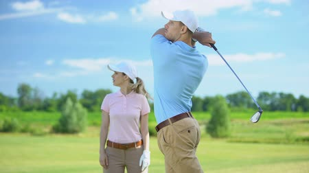 тренер : Man in sportswear hitting ball female partner rejoicing golf game victory, sport