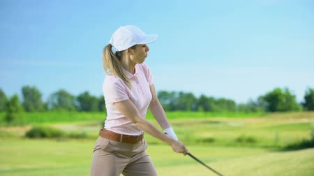 koers : Female in sportswear with golf club hitting ball suddenly feels lower back pain