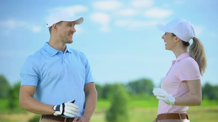 тренер : Flirting female and male golf players giving high-five after game, sympathy