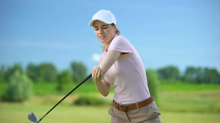the inflammation : Displeased female golfer feeling elbow sprain before ball hitting, sports injury