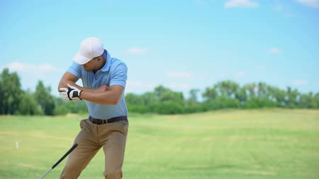 fatia : Male in sportswear playing golf, feeling elbow spasm, massaging painful area