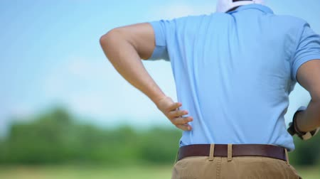 времяпровождение : Male golfer hitting ball in backswing position, feeling sharp lower back pain