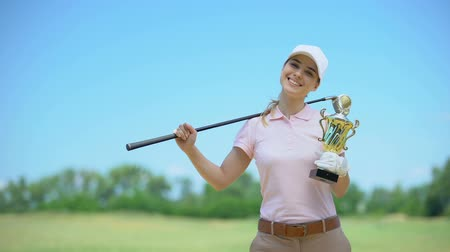 koers : Happy female golf player with club and gold cup smiling on camera, sport victory Stockvideo