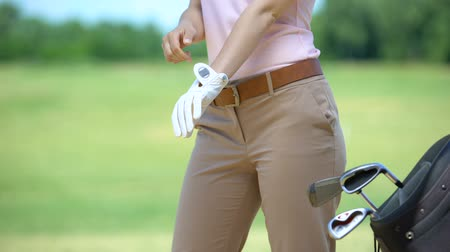 tomar : Skilled female golf player wearing white glove bag with iron clubs nearby, hobby
