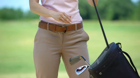 tomar : Professional female golf player wearing glove and taking club, ready to game