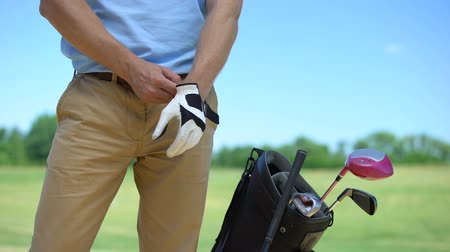 regulamin : Male golfer wearing white glove before game, bag with sports equipment nearby